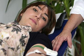 Foto: Eine Blutspenderin liegt bei Blutentnahme auf einer Liege.